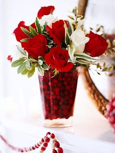 Fill a vase half full of berries and fresh water and insert an arrangement, such as these roses and holly leaves. Add more water and cranberries to hide the stems.  This would also be cool with fake flowers and candies, but no water then.