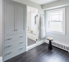 Beautiful bathroom features gray built-in linen cabinet stacked over built-in drawers over wood like tiled floor situated next to walk-in shower clad in subway tile shower surround accented with tiled shower niche over shower bench atop penny shower floor.