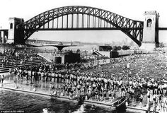 New Yorkers cool off in the Astoria public pool with the Hell Gate railroad bridge looming in the background in the summer of 1940.