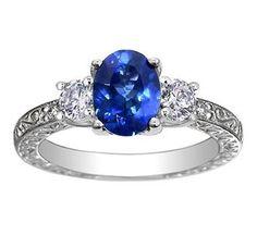 Sapphire Antique Scroll Three Stone Trellis Ring set with a blue oval Ceylon sapphire.