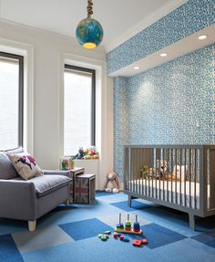 Blue and gray nursery design features Babyletto Hudson Crib in Grey leaning against accent wall clad in blue numbers and letters wallpaper atop blue and gray carpet tiles. Contemporary boy's nursery with gray glider paired with Union jack nesting tables illuminated by world globe light pendant suspended on rope.
