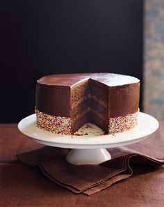Lizzie Kamenetzky's chocolate cake recipe is made with three layers of chocolate and soured cream sponge filled with a fluffy chocolate buttercream and coated in an unsweetened chocolate mousse icing.