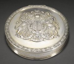 A George V silver-gilt Royal seal-box inkstand, Garrard & Co. Ltd., London, 1911 the lid with Royal Arms in full achievement within oakleaf borders, mounted glass well inside with sponge surround, engraved 'Presented to the Marquis of Crewe KG by King George V and Queen Mary on April 24th 1913'