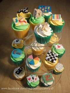 Cupcakes: Retro board games themed mini cupcakes. Cupcake tower. Handmade sugarpaste decorations; jenga, connect four, scrabble, battleship, chess, trivial pursuit, monopoly, dice, noughts & crosses, playing cards & snakes and ladders. www.facebook.com/thegrovecupcakery