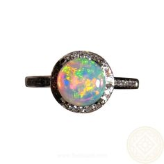 A pretty Opal ring for women that is shown in a 14k White Gold setting with a halo of pave Diamonds around the Opal and Diamonds around the side of the mount and on the band for a total of 75 Diamonds.  The round Coober Pedy Crystal Opal weighs almost 1.5 carats and shows a beautiful mix of colors in a unique 3D pattern.