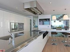 "My dream kitchen is in the ""Smart House"" I found on Zillow.com.  The stainless steel countertop and white cabinets make for a sleek, modern kitchen.  The bar stools are also a great feature"