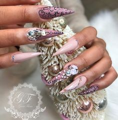 purple and pink with black detailing and crystals stiletto nails