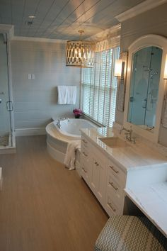 Stunning bathroom with tan colored wood paneled walls and a blue wood paneled ceiling adorned with a Worlds Away Chrialto Large Chandelier Pendant over the soaking tub.