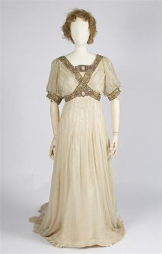 Evening gown of cream-colored satin, with over gown of cream-colored silk with woven indent sequins decoration with meander motif à la l'an...circa 1900-1910