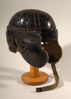 D&M leather football helmet c.1915-25. Very large full size black leather helmet with uncommonly shaped elongated ear flaps. Retains its D&M Lucky Dog logo stamping on a side panel. $1400