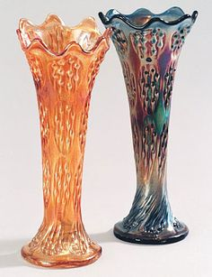 Orange and rainbow coloured tall vases, called knotted beads in carnival glass by Fenton.