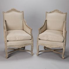 "Pair 19th Century French Painted Bergeres  --  Circa 1880 pair of upholstered French armchairs with painted and carved frames. Shell form crests, scrolled arms, decorative carved aprons, leaf form details on legs and criss cross stretchers. Newly upholstered in gray Belgium linen.  Arms are 25.25"" high, seats are 20.5"" high and 23.5"" deep. Sold and priced as a pair.  --   Item:  6480  --  Retail Price:   $4995"