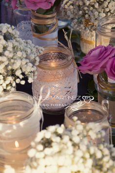 Botes decorados con flores y velas para las mesas. Centros de mesa