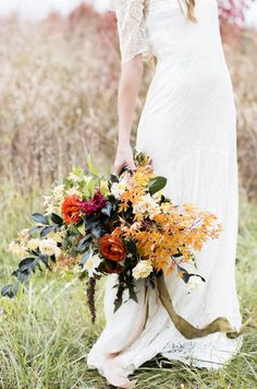 A fall wedding bouquet looks so pretty when layered with orange and yellow flowers. Add in some maple leaves and ferns to fit the season, too.
