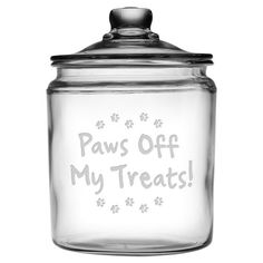 Perfect for stowing your four-legged friend's favorite treats, this charming glass jar showcases a sand-etched typographic and paw-print motif.