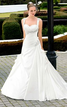 Style D1218 This sumptuous designer wedding gown is made of rich Dolce Satin and features strong pleating at the neckline and from the silver crystal spray accent at the hip. Detachable Diamante embellished shoulder straps included. Choose from a corset or zipper closure.