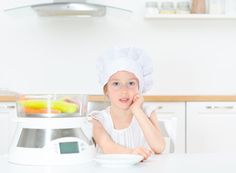 Little girl in chef hat with steamer in kitchen.