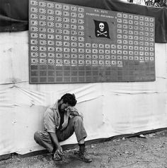 An exhausted American Naval pilot of the U.S. VF-17 unit pauses under the squadron scoreboard during the Bougainville Campaign (codename: Operation Cherry Blossom) against Japanese forces.