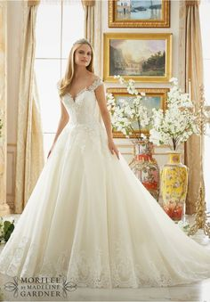Wedding Dresses and Wedding Gowns by Morilee featuring Frosted Beading on Alencon Lace with Wide Scalloped Hemline on Available in Three Lengths: 55 , 58 , 61 . Colors Available: White, Ivory, Ivory/Light Gold