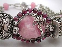 """Eni Oken.  Details """"Rhodochrosite is a stunning naturally rose or salmon colored stone -- it's name comes from the Greek meaning """"Rose Colored"""".         This beautiful nugget inspired me to combine it with rare Peruvian pink opal coins, intricate Balinese beads, garnets and pink jade."""""""