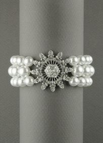 Cream three row stretch imitation pearl bracelet with floral detail is sure to add style to any outfit. Light Imitation Rhodium plating is sophisticated and rich; making the piece transition easily from day to night.  Material- manmade with white metal rhodiumfinish  Length- 7 inch ; 32.5mm width