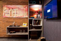 15 boas ideias para estantes e nichos da Casa Cor Campinas - A estante em cinza ganha cor e movimento com os nichos azuis e brancos. Com são vazadas, deixam visível o fundo de tijolinhos. Projeto de Simone Saviólli.