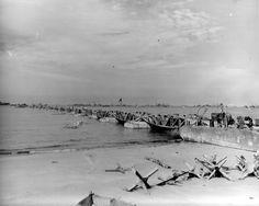 Le Mullberry A à Omaha Beach. Au premier plan, les hérissons du système défensif allemand que les éléments du US Engineers ont déblayés et rassemblés. Il s'agit probablement de la passerelle flottante (Whales) dite Eastern Pier, encore inachevée, le 18 juin, juste avant la tempête, à environ 300m à l'Est de la descente de Vierville-sur-Mer.