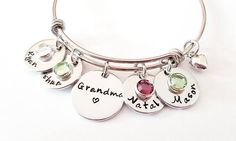 Show off your Grandma status with this beautiful stainless steel bracelet personalized with the name or names of grandchildren and their birthstone crystal. This would also make the perfect gift for the first time Grandma. ♥♥♥▬▬▬▬▬▬▬▬▬▬▬▬♥♥♥▬▬▬▬▬▬▬▬▬▬▬▬♥♥♥ Item Features: 1 - Stainless Steel adjustable/expandable bangle bracelet 1 - Handstamped Aluminum Charm - Grandma 1 - Name Charm - (choose more from the drop down menu) 1 - Swarovski Birthstone Crystal 1 - Silver puffy heart charm  ★★★...