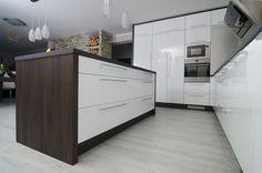 Bílý lesk tvoří s tmavým dřevěným dekorem a nerezí velmi zajímavou barevnou kombinaci příjemnou pro každé oko. Jednoduchý čistý design, ostrůvek pro pohodlnější vaření, uhlazenost, krása a čistota. Co více si přát.