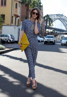 printed jumpsuit and oversized clutch