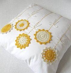 White and yellow pillow with crochet medallions, ribbon and embroidery.