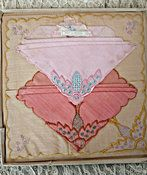 A set of three cotton embroidered hankies,pink, rose and yellow from the 1920's, or 1930's era. Each worked in the same embroidery style in different colors. The handkerchiefs are still attached to t