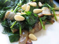Sauteed Spinach with Lemon, Garlic and Onions, and Pine Nuts    A few Tablespoons of olive oil  A half of an Onion, chopped  One garlic clove, minced  5-6 cups of Baby Spinach Leaves, washed and dried  A half of a lemon  1/4 cup of pine nuts  salt to taste