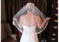 Hand-beaded fingertip length veil using Swarovski  rhinestones, pearls and sequins. Veil is attached to a fabric and clear comb.