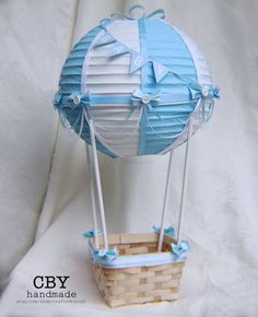 This beautifully handcrafted Hot Air Balloon centerpiece is made using a paper lantern that has been handpainted with alternating light blue and white segments. It is adorned with high quality light blue and White ribbons. It is decorated with white and light blue ribbon draping and embellished with light blue bows and white buttons. The lantern is attached to a basket that is decorated with light blue bows to match.  ** TWO STYLES TO CHOOSE FROM**  Tabletop (shown): The paper lantern is…
