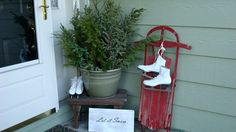 Christmas porch decorating with greens, a primitive bench, skates and an antique sled. Where's the snow?