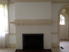 Living room fireplace (previous owner) showing arch into tiny front hall & front door.