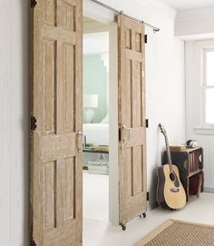 look of barn doors for fraction of the cost... attach caster wheels on bottom and screw hooks or large eye hooks into top and hang on conduit