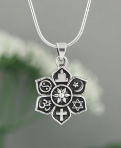 Lotus shaped sterling pendant represents harmony with symbols from major world religious. Made in Thailand.