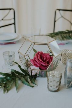 Glass terrariums filled with flowers are a pretty, modern alternative to traditional floral centerpieces | Image by John David Weddings