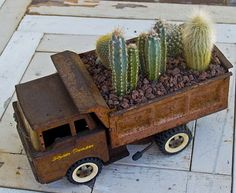 Rusty old truck for a planter box...I can see a row of these on a wall or along the edge of a garden. Love this idea.