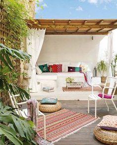 inspiratie voor een tuin in ibiza stijl. Combinatie van wit, hout en kleurrijke accessoires.