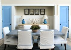 dining rooms - zinc topped table trestle blue piping cream slipcovered chairs doors beadboard seashells framed driftwood candle holder gourd lamps striped rug coastal nautical beach beachy