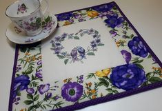 """Embroidered Wreath Candle Mat, Love Birds Quilted Table Topper, Purple Blue Yellow Green Floral Mug Mat, 12""""x12"""" by VillageQuilts on Etsy Quilted Table Toppers, Quilted Table Runners, Blue Yellow, Purple, Green, Bird Quilt, Table Runner Pattern, Mug Rugs, Hot Pads"""
