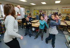 From left, Audra Colucci, a third grade teacher at Albany School, leads Jean Rivera, Jordann Brown, and James Beard, along with other students in fist pumping to multiplication tables, Jan. 21, 2015 in Utica, N.Y. Photo by: Mark DiOrio / Observer-Dispatch