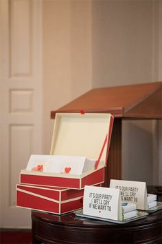 "Programs outlining the ceremony and introducing the bridal party were set out in red hinged-lid boxes from The Container Store. Along with the programs, mini tissue packs were wrapped with paper bands that said ""For Your Happy Tears"" with a stylized teardrop. They were set out on melamine trays along with a sign reading, ""It's our party and we'll cry if we want to."""