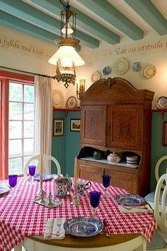 The dining room of this home in Boone, North Carolina captures the true Swedish country feeling. Some things to note are the high beadboard walls capped with a shelf, and the use of teals, reds and yellows. Here is a close up - notice the Swedish words painted on the walls, the cupboard and red check.