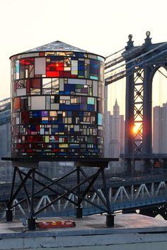 A Mondrian-inspired water tower glows like a jewel along the NYC Skyline. Amazing.