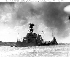 USS Raleigh (CL-7) after the attack on Pearl Harbor. She is being kept afloat by a barge lashed alongside. She sustained damage from a Japanese bomb and torpedo during the attack. The capsized USS Utahcan be seen in the background.