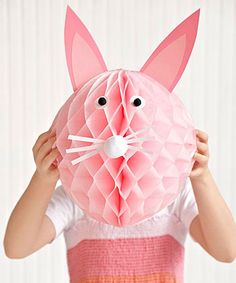 Why throw out old party decorations? A generic crepe paper ball can become an Easter bunny with the addition of craft paper ears, eyes, and whiskers, plus pom-poms for the nose and eyes.   - CountryLiving.com